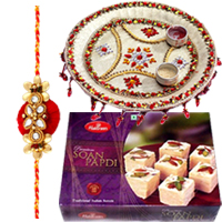 Ravishing Raksha Bandhan Delight of Mouth-Watering Soan Papri, Fantastic Thali and Rakhi along with free Roli and Tikka